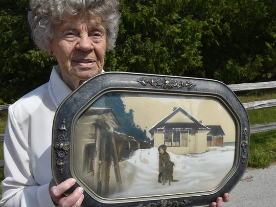 Judy Meneau holds a photograph of her and her dog Brownie