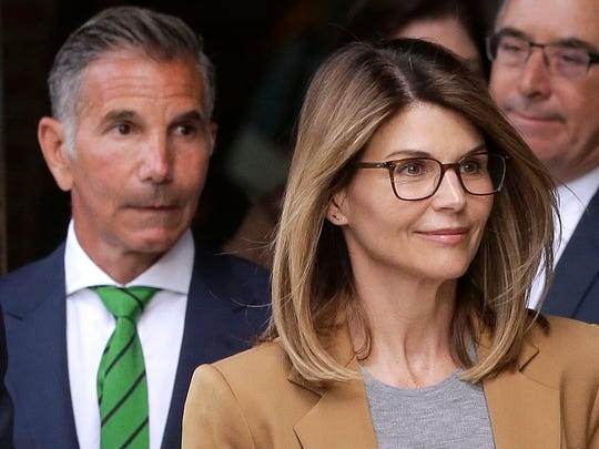 Actress Lori Loughlin, front, and husband, clothing designer Mossimo Giannulli, left, depart federal court in Boston on April 3, 2019, after facing charges in a nationwide college admissions bribery scandal.