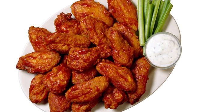 Buffalo wings are served with celery and blue cheese dressing.