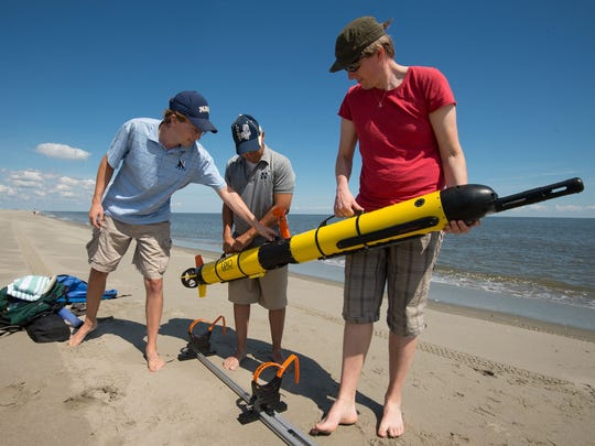 Preparing to test an underwater vehicle off Broadkill Beach on Aug. 24 are researchers (from left) Andrew Keppel, Luis Rodriguez and Tor Inge Loenmo. Researchers have had two water rescues in recent weeks.