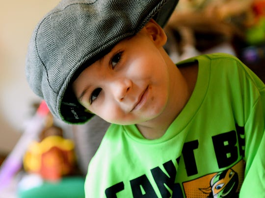 Kaleb Becker, 3, wears his dad's hat while playing in his Eaton Rapids home Friday, Sept. 30, 2016. Kaleb Becker was diagnosed with Acute Leukemia in August, the day of his father's 43rd birthday. The community is planning a fundraiser for the family.