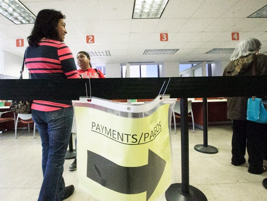 Amelia Casas, left, and Ana Zapata line up to pay their