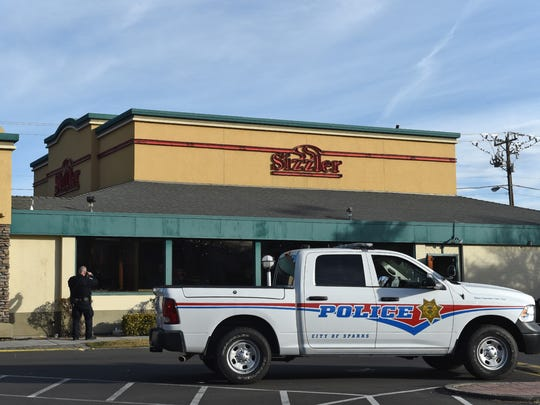 Police take a photograph of a broken window at the Sizzler in Sparks where police believed a suspect armed with a gun was inside the restaurant on Prater and McCarran on Jan 24, 2018. The incident ended when nobody was found in the building.