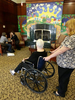 Last year, caregiver Kim Bauer pauses as the elderly woman she is helping looks at a decorative fire place at Cedar Village retirement community in Mason, Ohio. The woman she is helping has suffered abuse by a relative. The Shalom Center that is a part of the community helps by offering shelter, along with medical, psychological and legal help, to elderly abuse victims in this northern Cincinnati suburb. Eight such shelters have formed an alliance and are scheduled to meet to share best practices and hear from experts on elder abuse.