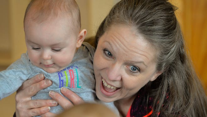 In-home child care provider Kelly Martini smiles as she holds Rose Loso, 6 mos., while playing with some of her charges Tuesday, March 29 at her Avon area home. There has been a decline statewide in the number of in-home child care facilities and a shortage, especially in infant care.