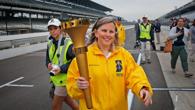 Jennifer Buechler carries the Bicentennial Torch, ready for the next leg from the Indianapolis Motor Speedway, Saturday, October 15, 2016.  The torch started the last leg of the statewide tour at the IMS, to end the route at the Statehouse with a big homecoming celebration.