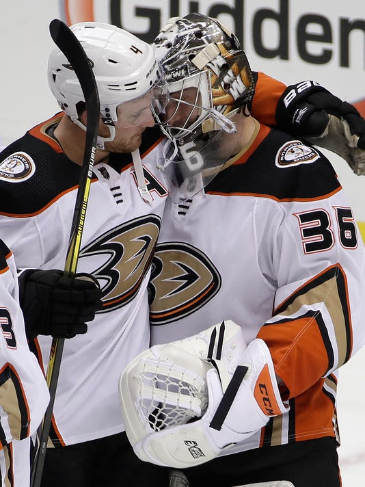 Anaheim Ducks goalie John Gibson (36) gets a hug from Cam Fowler (4) after earning a 4-0 shutout of the Pittsburgh Penguins in an NHL hockey game in Pittsburgh, Saturday, Dec. 23, 2017. (AP Photo/Gene J. Puskar)