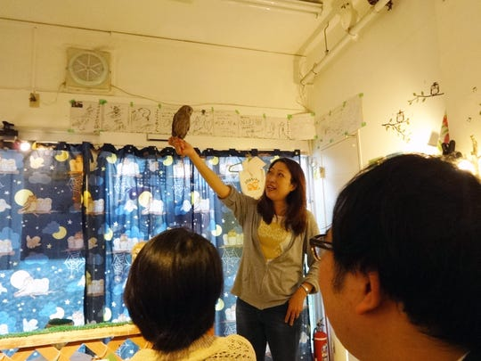 An employee of Fukuro no Mise (Shop of Owls) in Tokyo shows visitors the proper way to hold an owl.