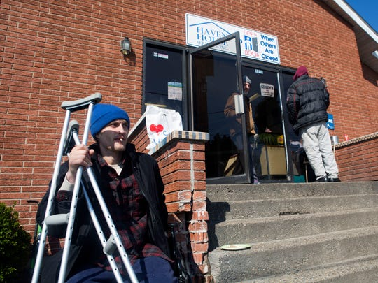 Skyler Kunkel, left, smokes a cigarette outside of Haven House homeless shelter before eating lunch at a nearby soup kitchen on Tuesday, March 14, 2017. Kunkel traveled to Haven House in Jeffersonville, Ind., because he disliked the mandatory prayers at a religious-based shelter in Indianapolis.