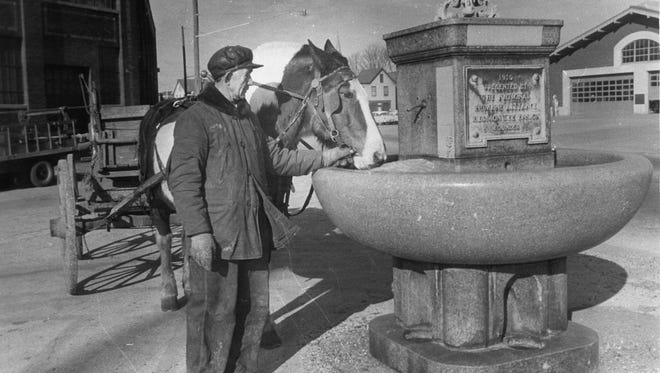 In this January 1960 photoa a horse is brought to drink from the fountain, what was once a horse trough, for the first time in decades, only to find the water frozen.