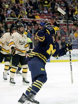 Michigan's Alex Kile celebrates a goal by teammate Cutler Martin during the first period.