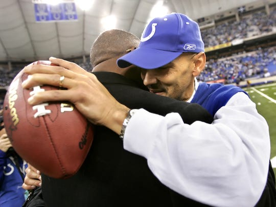 Colts head coach Tony Dungy holds onto the game ball as he gets a consoling hug by Larry Fitzgerald who's son is wide receiver Larry Fitzgerald for the Cardinals after the Colts win, Jan. 1, 2006.