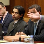 Defendant Derek Medina, center, sits in Miami-Dade court Tuesday for opening statements in his murder trial. Medina says he shot his wife in August 2013 in self-defense before allegedly posting a photo of her body on Facebook.