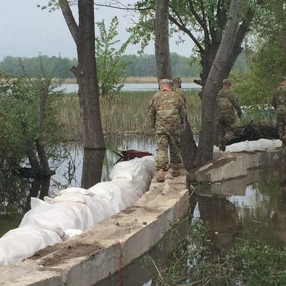 National Guard troops inspect their work on a retaining