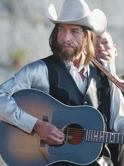 Bob Dylan, sporting a wig, performs at the Newport Folk Festival in 2002. (