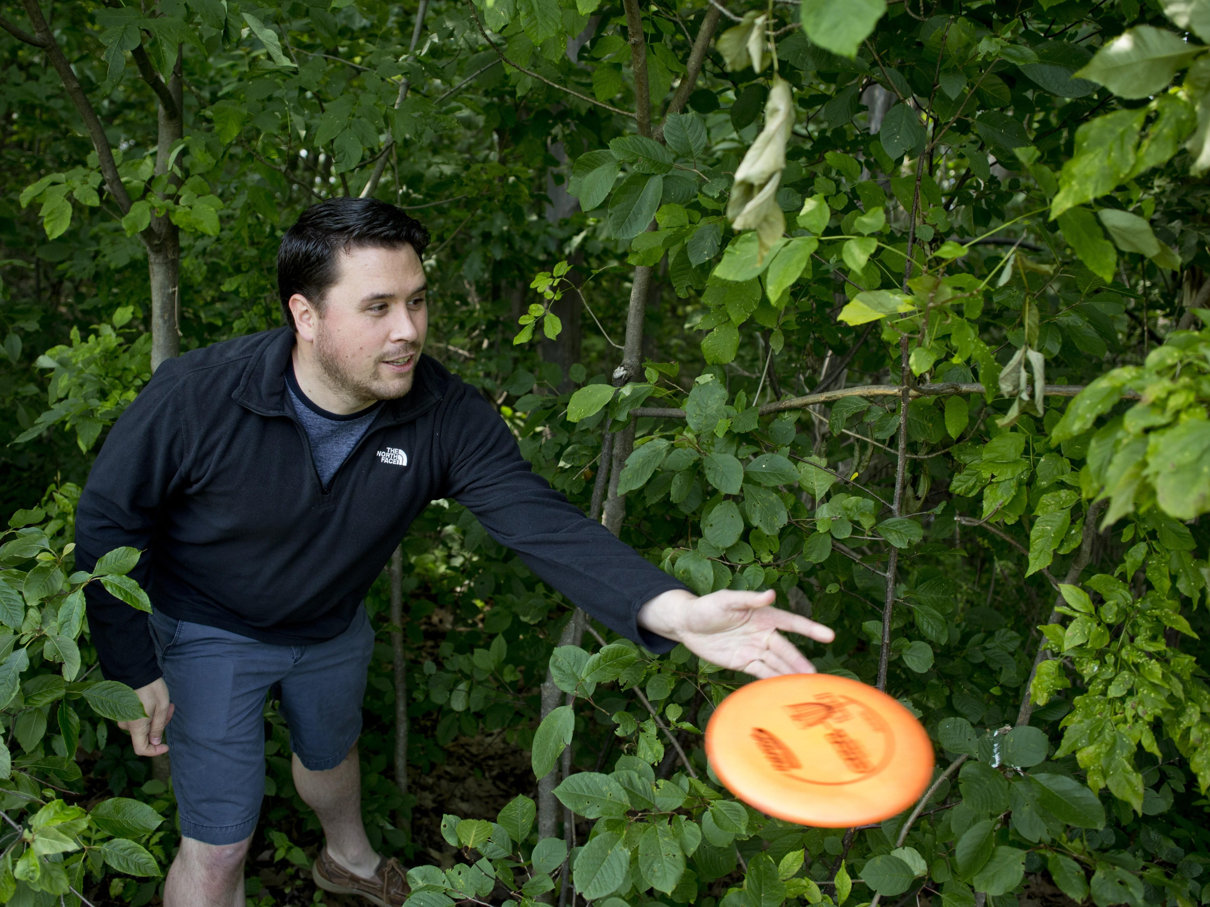 Paul Costanzo takes a shot around a tree line while playing disc golf Friday, July 3, 2015 at Holland Woods in Port Huron.