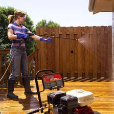 A woman cleaning off overspray by rinsing the siding and windows with clean water at a low pressure to remove chemical residue.