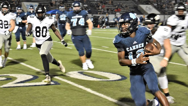 Camden County quarterback Joshua Brown (12) is chased down by Richmond Hill defenders during the teams' season opener Friday night in Kingsland. Richmond Hill won 28-11.
