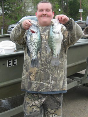 Josh Price of Smyrna holds his world record white crappie in his left hand, which he caught in Mississippi's Grenada Lake.