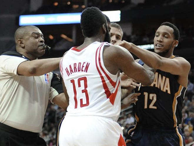 Referee Tony Brothers, left, tries to break up a confrontation between Houston Rockets' James Harden (13) and Indiana Pacers' Evan Turner (12) during the first half of an NBA basketball game Friday, March 7, 2014, in Houston. Both players received a technical foul.