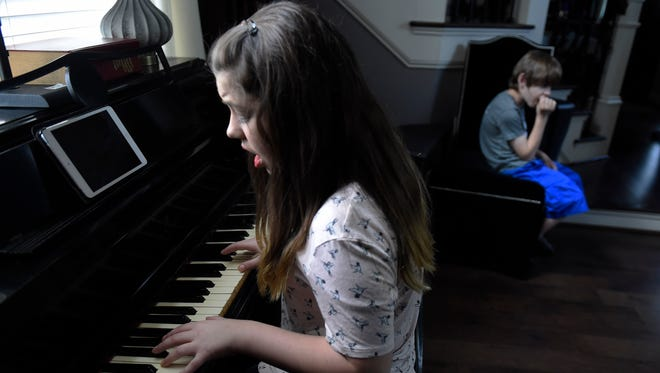 Lilah Petersson plays a song for her brother, Liam, at their Nashville-area home. The Petersson family founded Rock Your Speech, which incorporates speech therapy into music, after Liam was diagnosed with autism spectrum disorder.