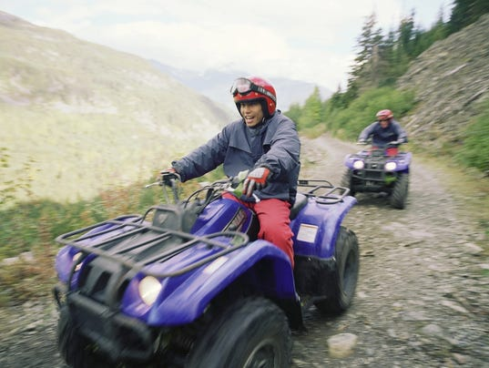 Couple riding ATV's on dirt road in mountains, blurred motion