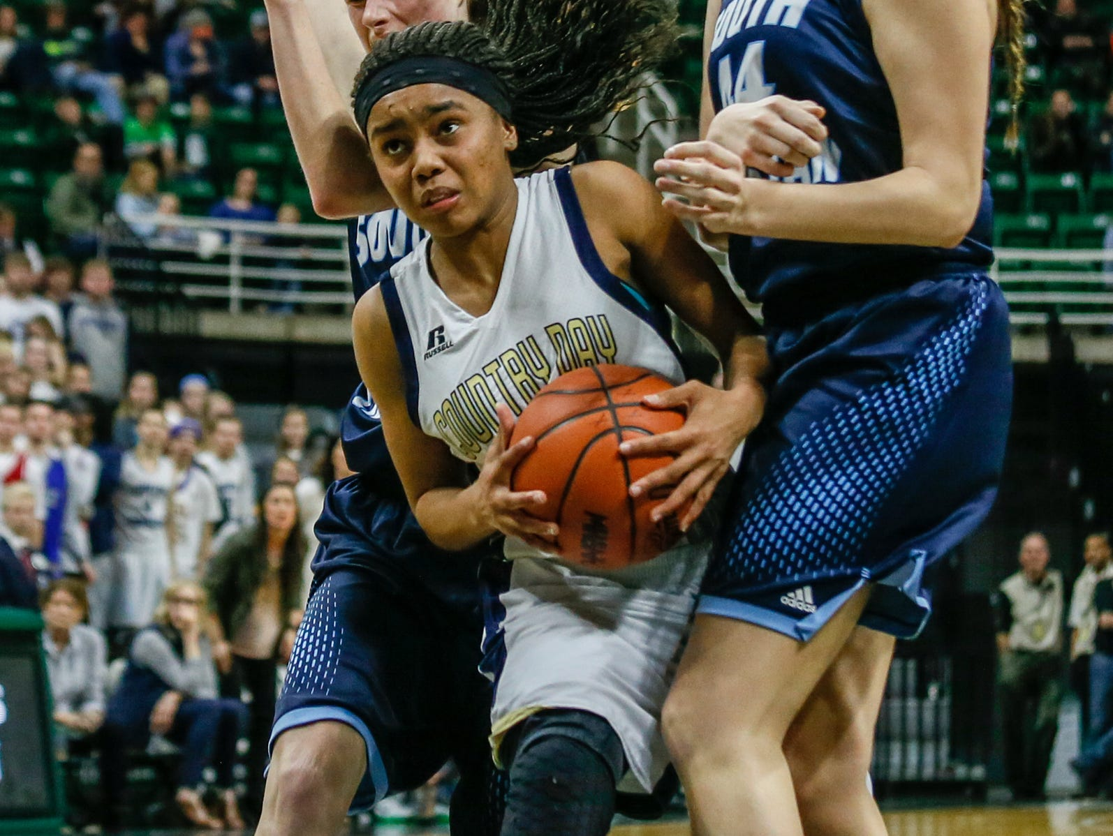 Detroit Country Day's Kaela Webb cuts through Grand Rapids South Christian's Mariel Bruxvoort and Isabella Scott's defense, during the second half of the MHSAA girls basketball Class B game 1 semifinals at the Breslin Center in East Lansing, Mich. on Friday, March 18, 2016.