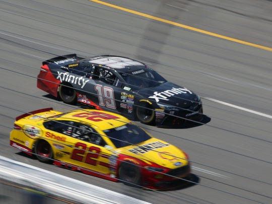 Carl Edwards (19) competes against Joey Logano during