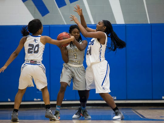 Barron Collier's Jada McCray (20) and Brittany Holmes (24) press Golden Gate's Chim'sly Pericles in the first half of action during the Class 7A-District 12 title game Friday, Feb. 3, 2017 in Naples. Barron Collier led 31-13 at the half.