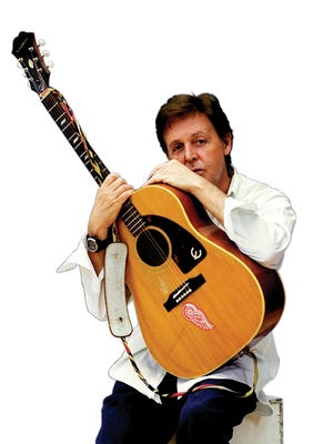Paul McCartney and his Epiphone Texan guitar, complete with Detroit Red Wings logo. This promotional photo was shot prior to 2010, when McCartney added a Pittsburgh Penguins sticker to the guitar.