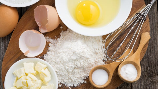 prepared fresh baking ingredients on a wooden board, horizontal, top view, close-up