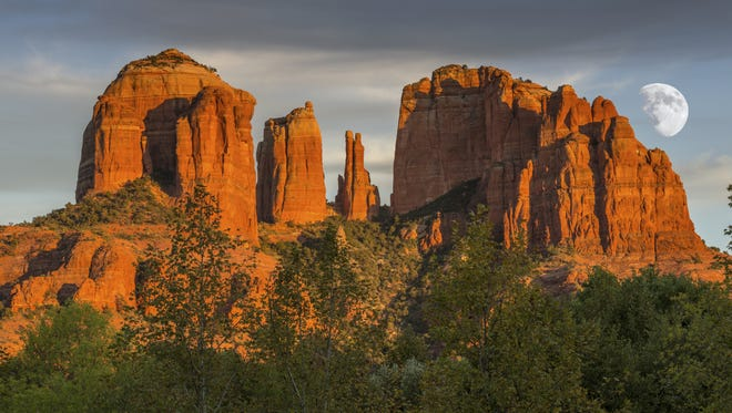 The sun sets on the Red Rocks of Sedona before being illuminated by the moon.