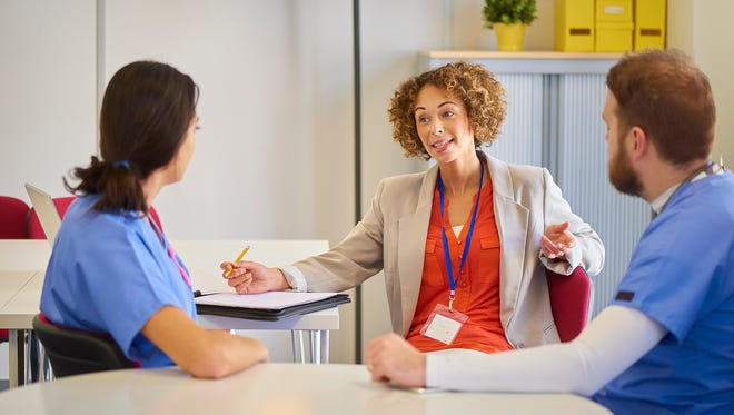 two male and female doctors chat in an office at the hospital to a female administrator . She is asking questions and taking notes .