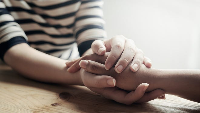 A woman consoles her friend by holding her hand