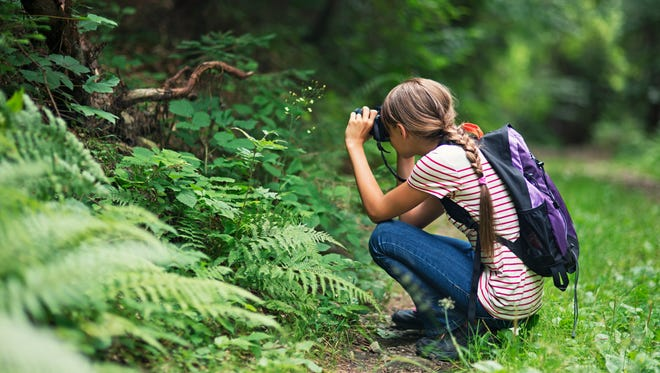 Girl taking photos in the forest