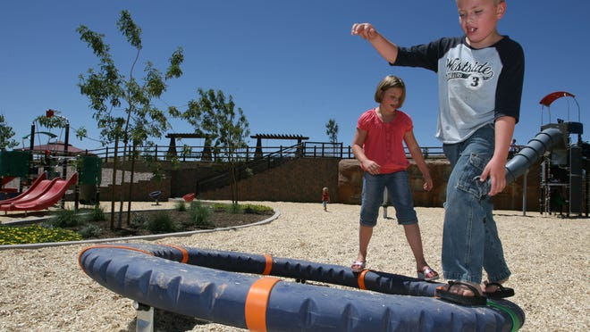 Jaxon King and Taylor Shiner try out walking on a spinning piece of playground equipment Friday at Cottonwood Cove Park in St. George. Washington County voters will vote in the Nov. 4 election on Proposition 3, a proposed sales tax increase that could generate an estimated $2.2 million annually to help fund parks, theaters, athletic facilities, campgrounds, swimming pools and other local arts and recreation amenities.