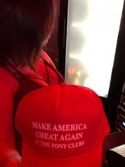Door host Brittney Hooten shows off the caps given to customers at The Pony Monday night for the Stormy Daniels appearances.