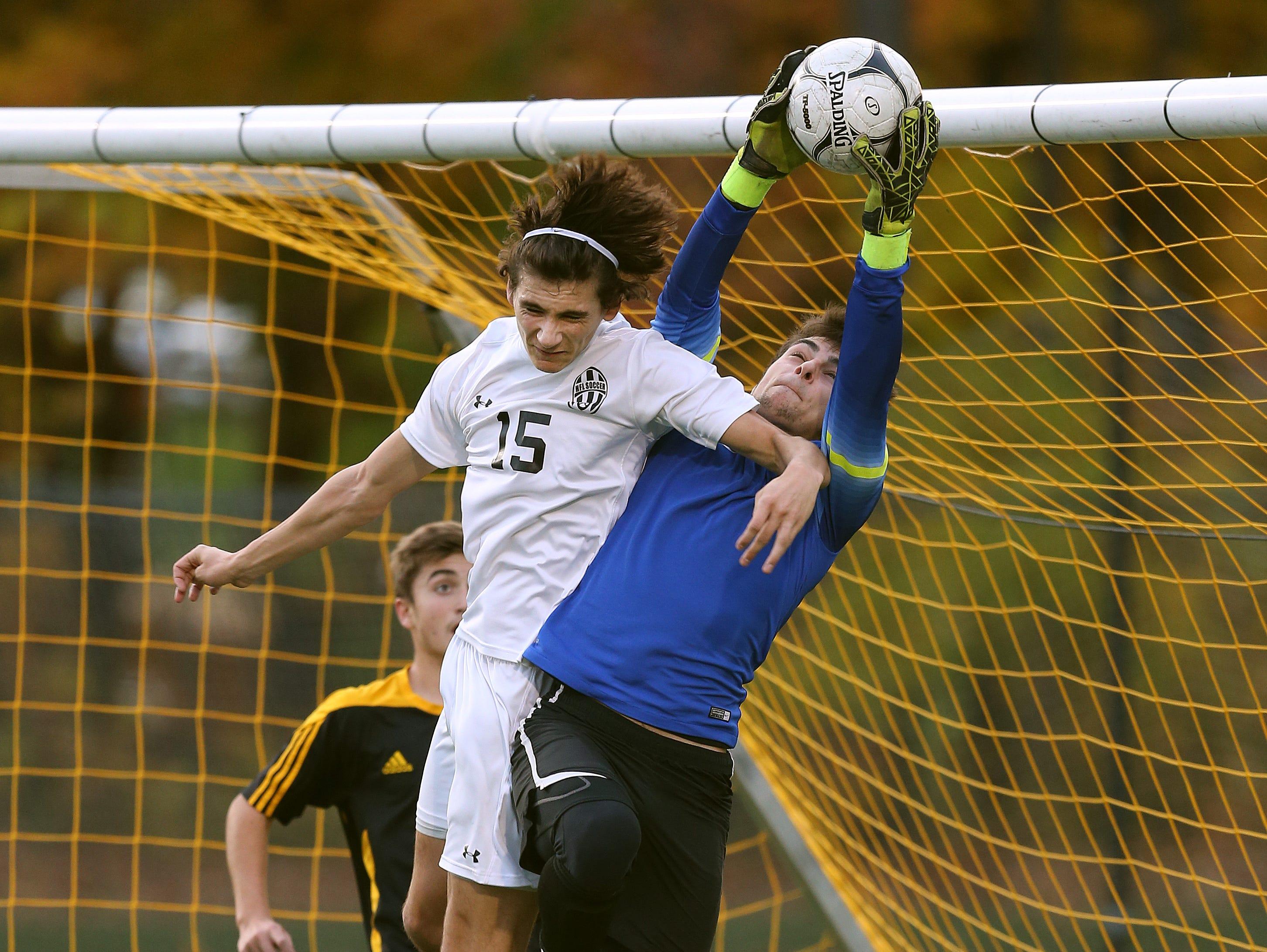 Athena goalie Thomas Pupatelli collides with Honeoye Falls Lima's Kieran Papalia (15) in front of the net.