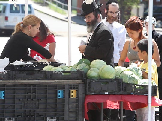 People from different cultures shop together at the Spring Valley Farmers Market at Memorial Park in July.