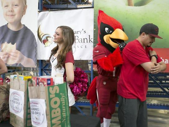 Arizona Cardinals mascot Big Red signs a football for