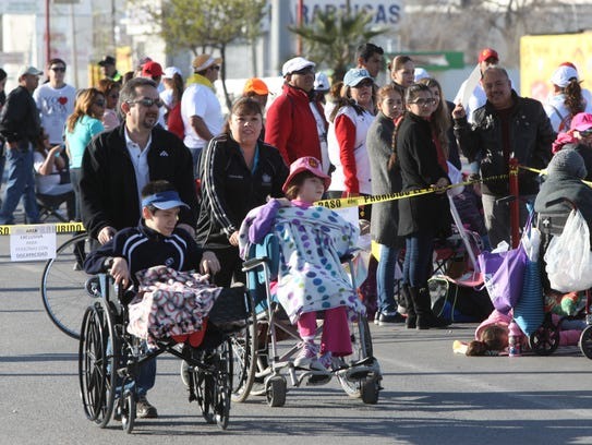 Adults push children in wheelchairs Wednesday as they