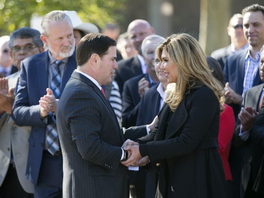 Arizona Gov. Doug Ducey shakes hands with the governor