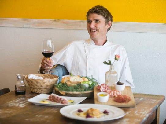 Chef Brian Konefal holds a glass of wine with some