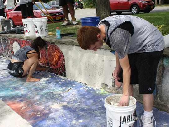 Emily Jablon and Eli Gaccione work to install a mosaic