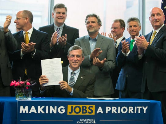 Gov. John Carney holds up the document after signing