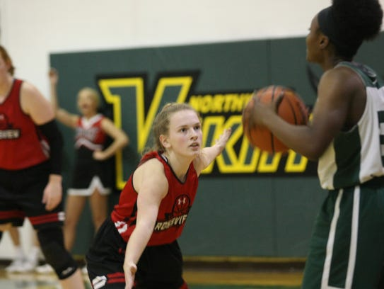 A Rossview player defends Northwest during their basketball