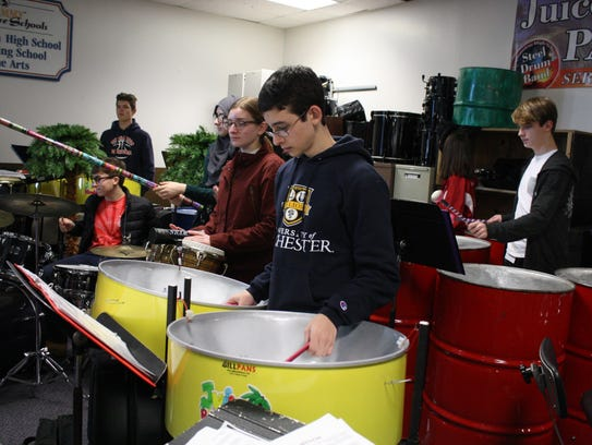 Joe King (in navy) play the bass pans during a Nov. 30 rehearsal of the Binghamton High School Juice Blenders Steel Drum Band.