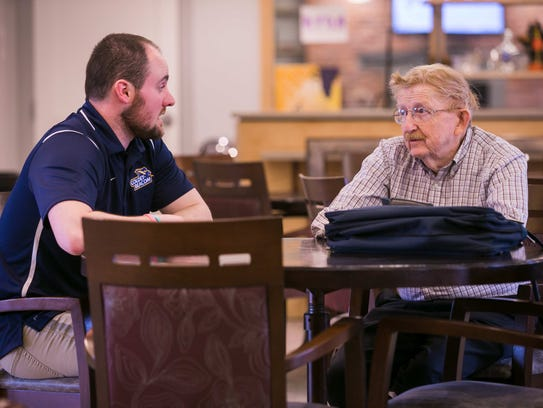 Jeremy Benoit, assistant athletics director at Goldey-Beacom College, talks to a veteran at the at the nearby retirement community, The Summit. Students have been recording the veterans' stories and will be transcribing them and turning them into a book.