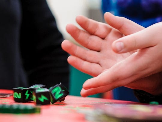Gamers roll the dice during a game.