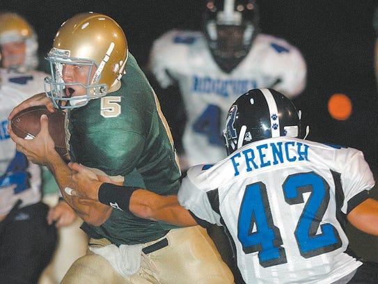 Nease quarterback Tim Tebow slips around Ridgeview's